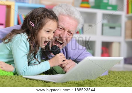 Grandfather and granddaughter lying on floor with laptop