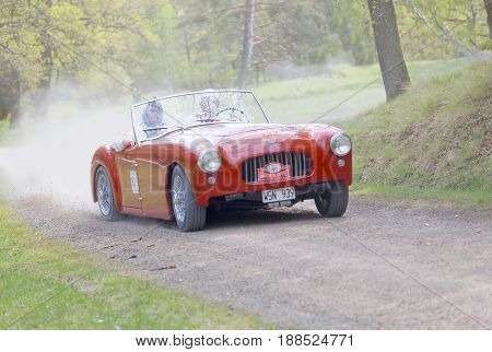 STOCKHOLM SWEDEN - MAY 22 2017: Red Allard Oetta classic car from 1953 driving on a country road in the public race Gardesloppet in the forests at Djurgarden Stockholm Sweden. May 22 2017