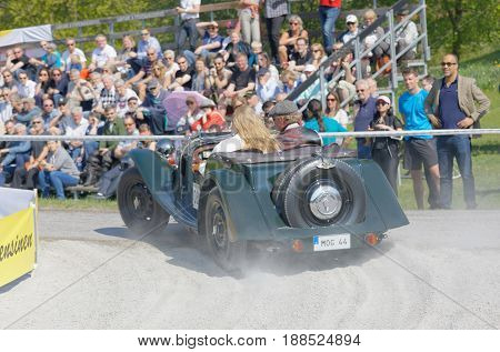 STOCKHOLM SWEDEN - MAY 22 2017: Rear view of a dark green Morgan 4-4 two seater classic car from 1936 driving in a curve in the public race Gardesloppet at Djurgarden Stockholm Sweden. May 22 2017