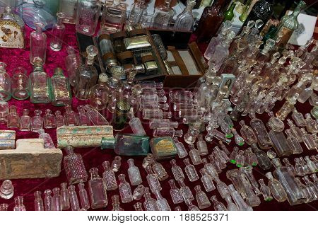 Moscow, Russia - March 19, 2017: Table at the flea market with empty vintage bottles and flacons of glass for wine, oil, medicines and perfumes of various sizes and colors