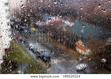 Raindrops on the window with a street in the backgroung