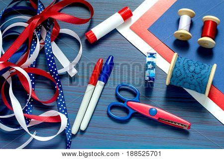Set of materials and tools for making handmade souvenirs and gifts by July 4 celebration of Independence Day. Paper and ribbons are blue white and red. Glue markers scissors on blue background