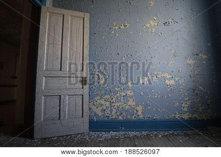 An empty room with door open of an old Asylum