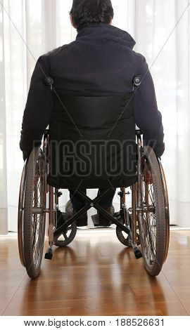 Handicapped Person In A Wheelchair In His Bedroom