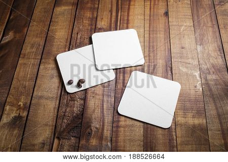 Blank square beer coasters and coffee beans on vintage wood table background. Responsive design mockup.