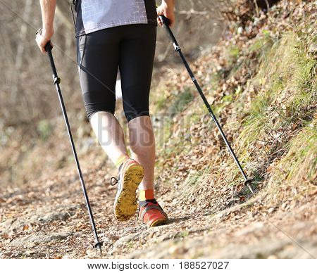 Young Runner Runs In The Mountains With Nordic Walking Sticks On