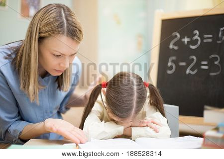 Preschool Home Education. Beautiful Young Girl Is Teaching At Home With Exacting Mother.