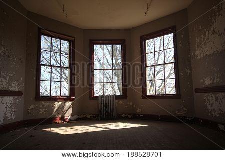 Three windows with a light shinning on the floor
