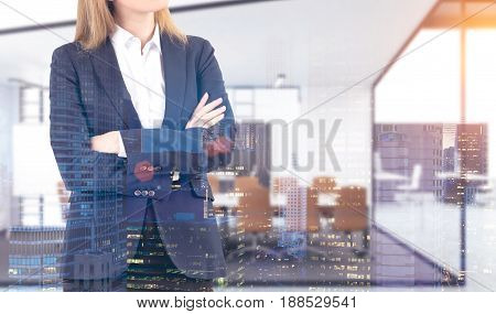 Close up of an unrecognizable powerful businesswoman in a blue suit standing with crossed arms in a city office. Concept of a successful career. 3d rendering toned image double exposure