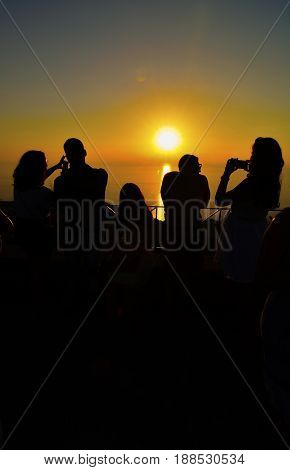 Silhouettes of people at viewpoint on the top of the hill watching and photographing sunset over the sea
