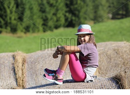 Nice Little Girl With Long Hair Over Hay Bale In The Countryside