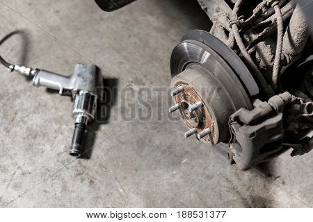 Closeup disc brake of the vehicle for repair. shot wheel, the tool for loosening the nuts. internal screw.