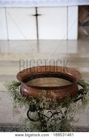 Baptismal Font In Copper Decorated With Flowers During The Relig