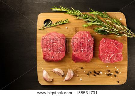 Three slices of raw meat, beef fillet, shot from above on rustic textures with a sprig of rosemary, garlic cloves, salt, and pepper