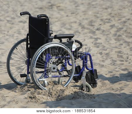 Wheelchair With Wheels Locked In The Sand Of The Beach