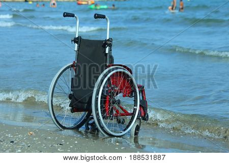 Wheelchair On The Shore By The Sea On A Sunny Day