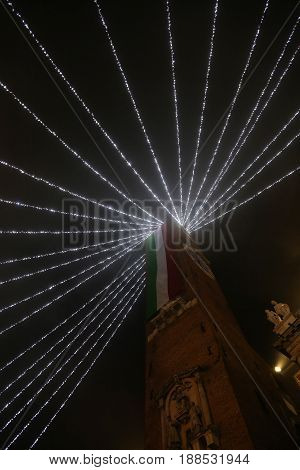 High Bell Tower With Huge Italian Flag With Christmas Lights In The City Of Vicenza In Italy