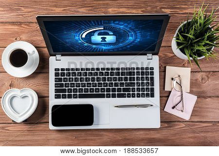 Business workplace with office stuff and laptop with padlock icons on screen