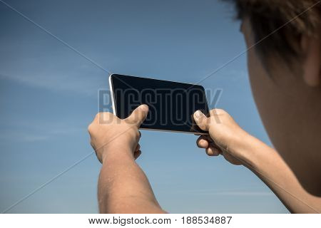 Child taking photo with his smartphone. Back view. Close up