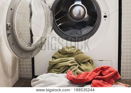 Washing machine with multicolored dirty towels on the floor near it. laundry washer with opened door. Frontal view. Close up