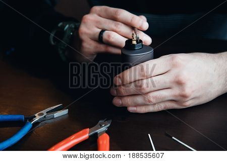 Master man sets up a spiral coil for the electronic evaporator and cigarette. On the table are wire, pliers, coils, screwdrivers. Concept Vape, vaping.