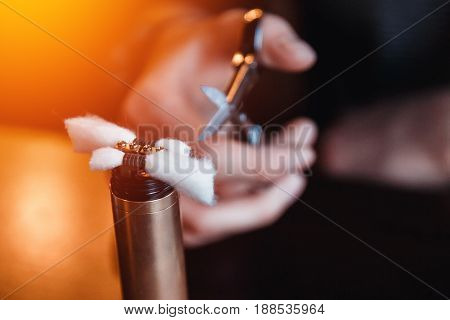Vape.male master installed cotton wool to refuel the electronic cigarette and cut with scissors.vaping device