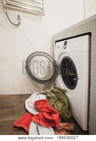 Washing machine with multicolored dirty towels on the floor near it. laundry washer with opened door. Side view. Vertical