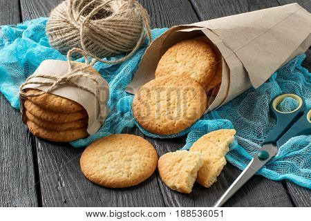 Delicious homemade cookies with onion sesame and spices in paper bag on table with blue gauze napkin. Twine and scissors for packaging