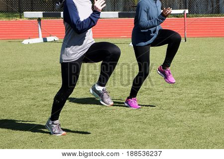 Two high school girls do A-Skips during track and field practice