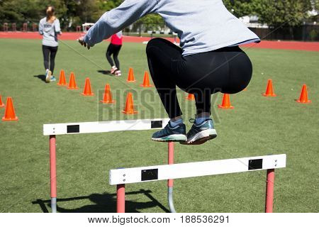 High school girls working out on a turf field by jumping over hurdles and doing running drills over orange cones.