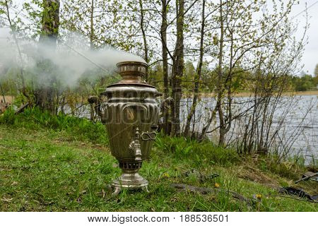 The samovar stands on the grass on the bank of the reservoir. The wind blows away the smoke from the samovar.