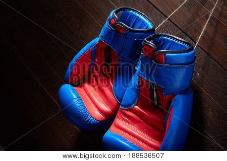 Close-up of the pair of blue and red boxing gloves hanging in a wooden wall. Horizontal photo and brown background. Sportive exercise and boxing training. Boxing backgrounds and still-life. Concept of the sportive life.