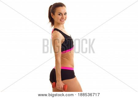 athletic young brunette girl with dumbbells in hands smiling on camera isolated on white background
