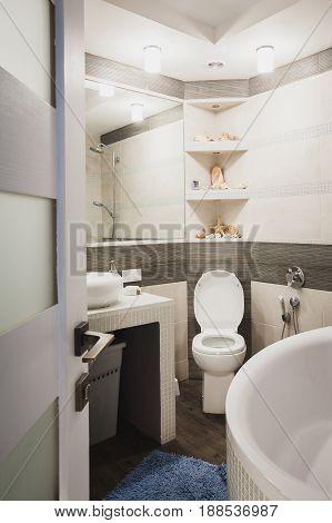 Interior design of a luxury bathroom, washroom with washbasin (sink), bathtub, huge mirror and seashells on the shelf. Vertical