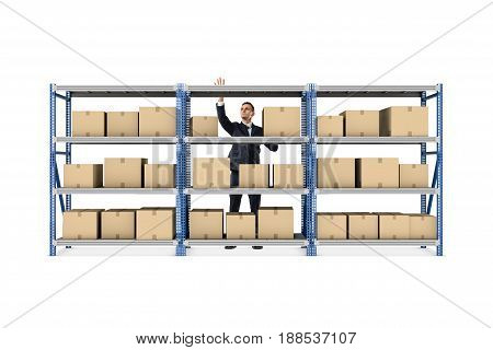 A businessman standing behind a metal warehouse rack full of boxes on white background. Goods and merchandise. Taking stock. Delivery and packing.
