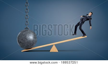An unbalanced businessman standing on a wooden seesaw and overweighed by a wrecking ball. Unfair disadvantage. Weight of problems. Unresolved complications. poster