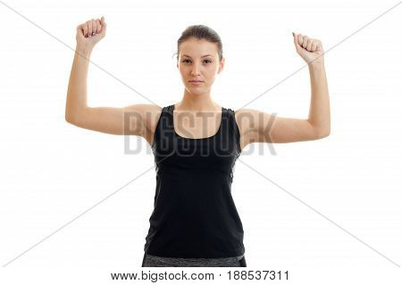 Serious young girl in sports uniform with hands in the air looking at the camera isolated on white background