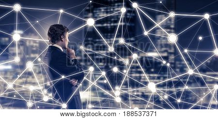 Businessman against night cityscape looking at social connection media concept