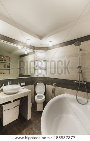 Interior design of a luxury bathroom, washroom with washbasin (sink), bathtub, huge mirror and seashells on the counter.