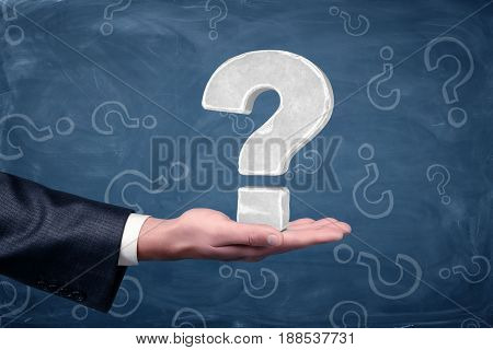 A businessman's hand holding a large white question sign palm up on blue chalkboard background. Problems and solutions. Business cases. Problem solving skills.