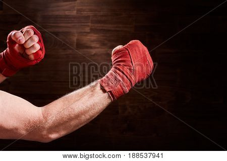Close-up of hands of boxer with red bandage ready for a fight against brown wall. Horizontal photo and wooden background. Boxing training and exercise. Sportive backgrounds. Concept of the sportive lifestyle.