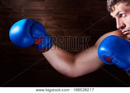 Portrait of young boxer fighter with boxing gloves against wooden wall. Horizontal photo and brown background. Boxing equipment. Sportive exercise and training. Energy, power and motivation. Concept of the sportive lifestyle.