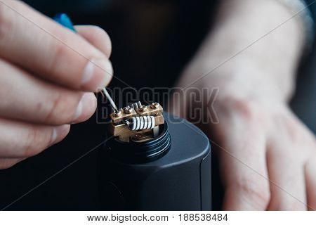 male master installs a coyle. Spiral for electronic evaporator and cigarette. Vape, vaping. Firing a coil.