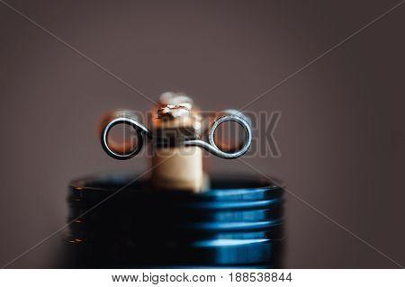 Coil spring close-up on a dark background. Vape, vaping. Firing a coil.