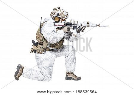 Special forces operator of Navy Seals armed with assault rifle with closed face in polarized sunglasses and military winter camo clothes shooting in kneeling position. Studio shot