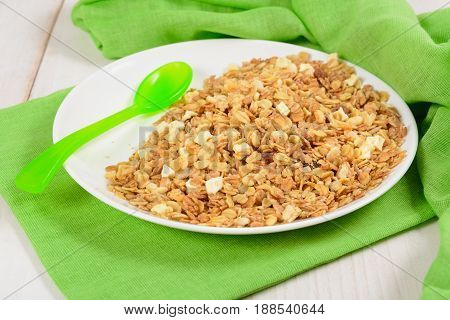 Granola On White Plate With Green Plastic Spoon Like Breakfast For Kids