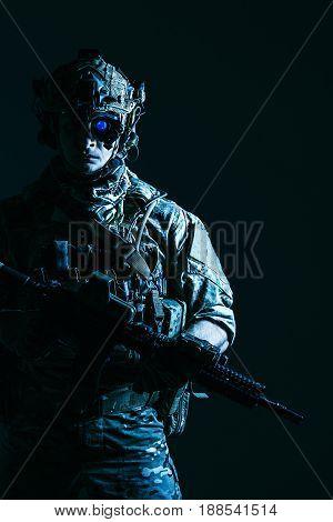 Elite member of US Army rangers in combat helmet and night vision device. Studio shot, dark black background, looking at camera, dark contrast