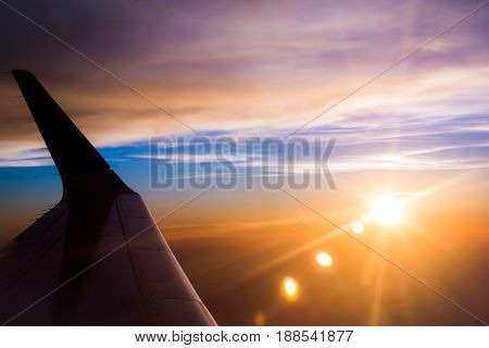 aero plane wing with sky and sunlight flare background in twilight time
