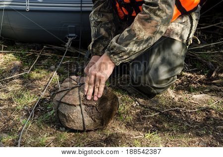 The fisherman makes an anchor of stone. He ties the stone with a rope.