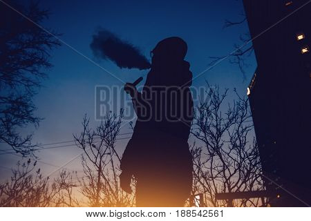 vaping man holding a mod device. cloud of vapor. Vape. high contrast and monochrome color tone.